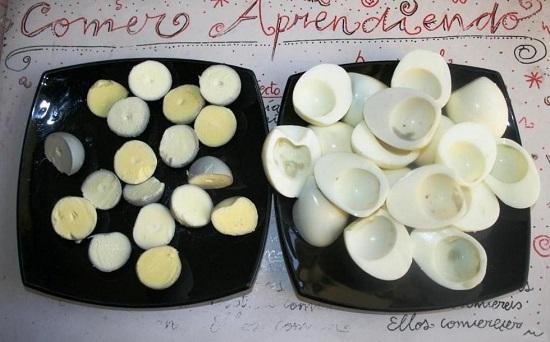 Аккуратно разрезаем яйца пополам и убираем желтки